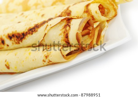 Crepe roll up a tubule on a plate. It is isolated on a white background.