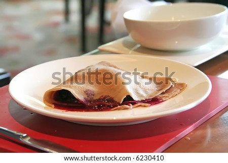 Crepe with jam filling on white plate in restaurant