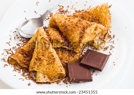 crepes with chocolate and dessert spoon on white table