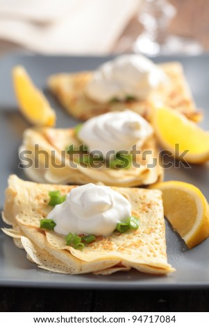 Crepes with cream fraiche, green onion and lemon #94717084