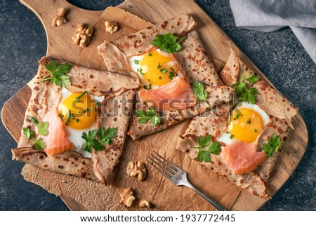 Crepes with eggs, salmon, spinach and nuts. Traditional dish galette sarrasin or buckwheat crepe, french brittany cuisine. Foto stock ©