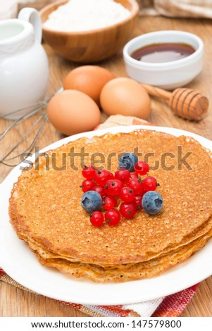 crepes with fresh berries and ingredients for baking close-up vertical