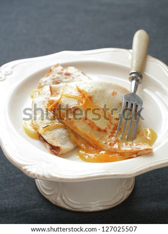 Crepes with honey or sirup and orange, selective focus
