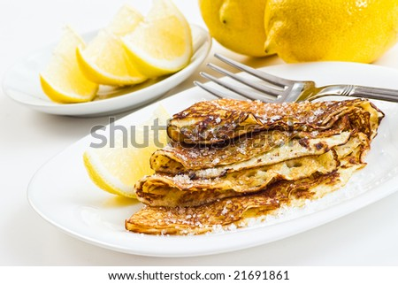 crepes with lemon and sugar on white plate