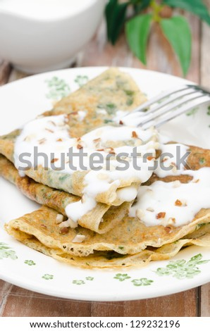 crepes with spinach with yogurt sauce and nuts on a plate vertical