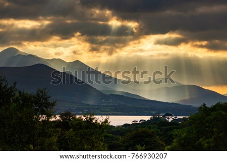Shutterstock Crepuscular rays also known as Rays of God streaming through gaps of dramatic clouds over The Reeks in Kerry Southwest Ireland