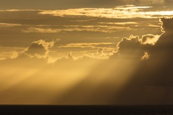 Crepuscular rays of the setting sun stream through a dark monsoon cloud bank hanging above the sea off the coast in Gokarna in India.