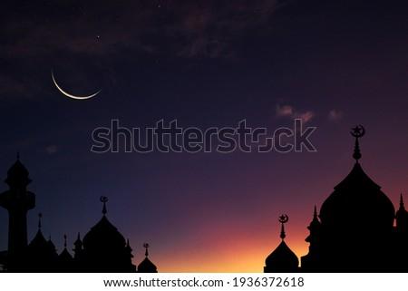 Crescent moon sky on dark blue dusk over Islamic mosque silhouette,Twilight Sky in the Evening with Sunset and Beautiful Sunlight on dark cloud ,Hari raya festival,Eid al-Adha, Eid al-Fitr, Muharram.