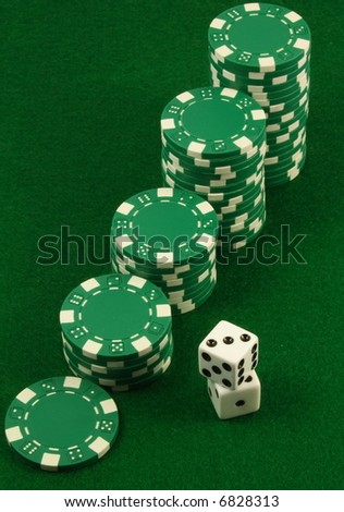 Crescent piles of green poker chips over a green table and besides two white dice.