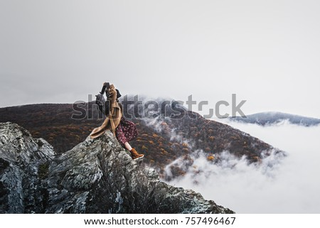 Stock Photo Crescent Rock Overlook along Skyline Drive in the Shenandoah National Park, woman with hat, backpack, winter jacket and cellphone has this inspirational view across  foggy valleys and mountains below