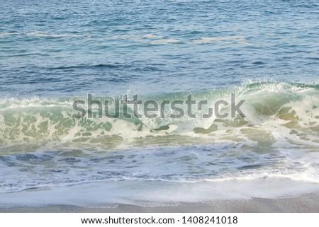 cresting breaking wave on shoreline edge with washback foam on sandy shoreline
