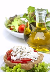 cretan recipe(dakos),roasted bread with a topping of tomato cubes and  feta cheese, green salad and olive oil(vertical)