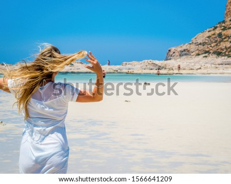 Crete, Greece: Blonde beautyful girl enjoying the beautiful crystal clear sea of Balos lagoon. Lagoon of Balos is one of the most visited tourist destinations on west coast of Crete. #1566641209