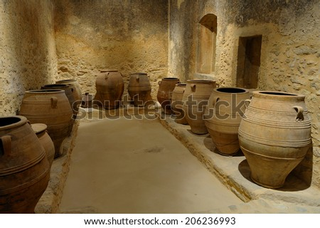 Crete, Greece, February. 3. 2009: Old olive oil factory with stone mill and ancient vase, island of Crete, Greece