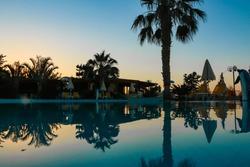 CRETE SWIMMINGPOOL PALMTREE REFLECTION DURING SUNSET ON HOLIDAY