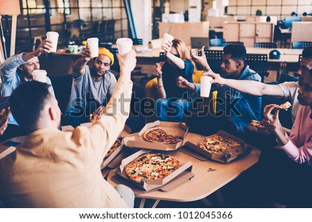 Crew of employees celebrating successful startup raising cups with beverages cheers with each other, male and female coworkers having pizza party after hard working day using team building concept