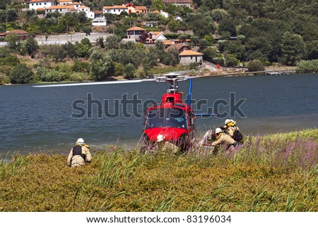 Crew of firefighters working on the helicopter stopped on the banks of the River Douro