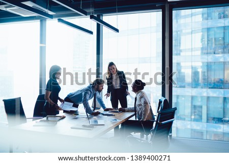 Crew of intelligent male and female having meeting table for discussing business startup ideas share opinions, brainstorming of clever professional employees teamworking at office interior