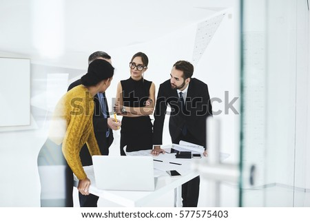 Crew of skilled marketing experts consulting with executive about rebranding of corporation suggesting new advertising campaign to change style sharing opinions on formal meeting in conference hall