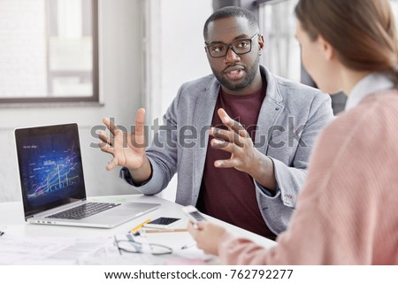 Crew of talented young employees explain ideas during working meeting. Black male employer shows financial presentation, analyze graphics, gestures with hands, look attentively at interloutor