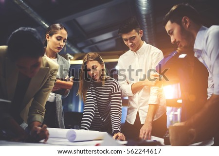 Crew of young male and female architects creating blueprint for modern constructed building consulting with skilled teacher correcting mistakes and giving advice during training lesson in university