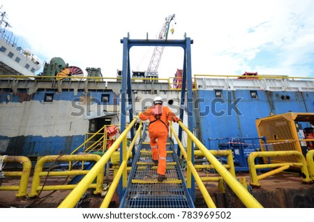 Crews crossing gangway between accommodation barge and material barge