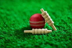 cricket ball and bails on green grass pitch