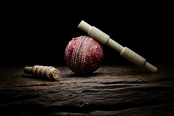 Cricket ball and wickets still life close-up on a highly texture wooden surface. Stock