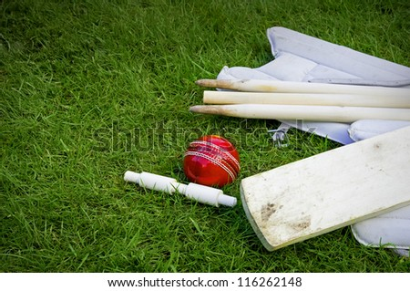 cricket ball, bat & pads with stumps and bail on grass