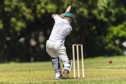 Cricket Batsman Action Cricket game closeup player batting ball stroke strike action high school teams.