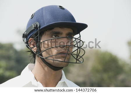 Cricket batsman wearing a helmet - stock photo