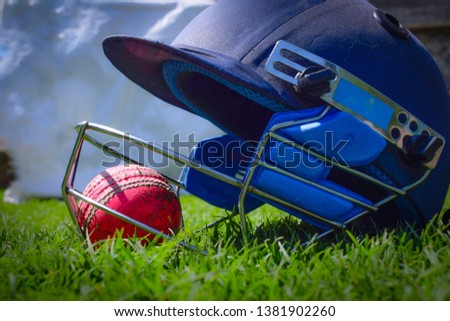 Cricket halmet and a ball on a green grass. Helmet protects batsman from fast balls which may otherwise cause harm to playing person. #1381902260