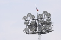 Cricket stadium floodlights at day with blue sky, High power spotlights, grandstand and outdoor Cricket pitches in the evening in Delhi India
