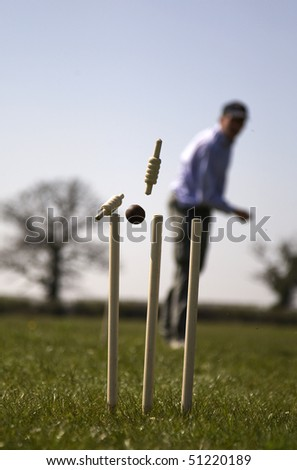 cricketer hits the stumps with his ball