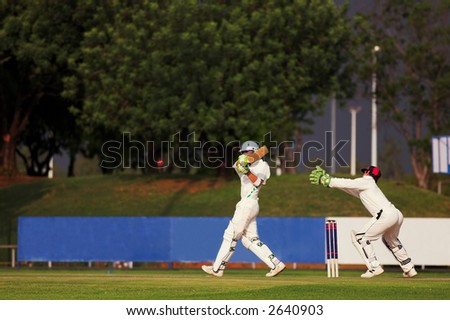Cricketers playing in the late afternoon, Batsman hitting ball, wicketkeeper trying to catch