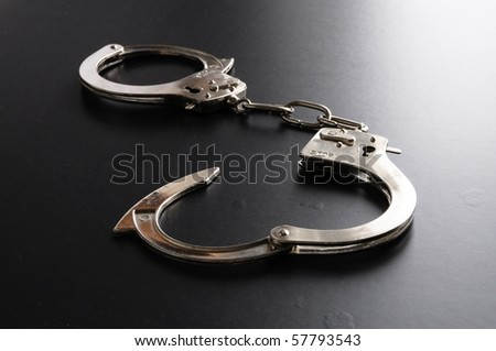 crime and law concept with police handcuffs on desk
