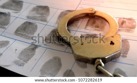 Crime and violence concept.Police Handcuffs on  fingerprints crime page file