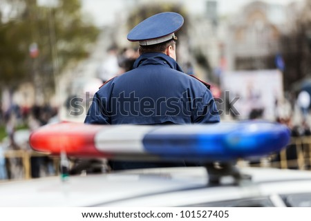Crime law security service officer cop guarding street near police car with siren light
