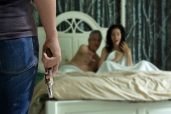 Crime of passion husband with gun has caught his cheating wife in bed with her lover and he is about to shoot and kill them or run the boyfriend out of his house or intruder committing crime.