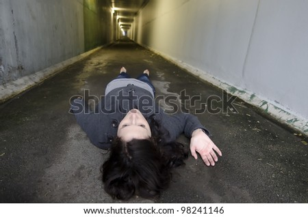 Crime scene concept photo of a murder victim woman lying dead on the ground of a tunnel.