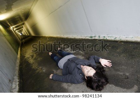 Crime scene concept photo of a murder victim woman lying dead on the ground of a tunnel. Concept photo of murder and crime