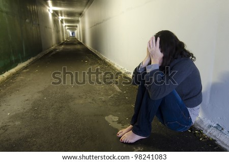 Crime scene concept photo of rape victim. A sad woman sits on the floor of a dark tunnel.