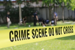 crime scene do not cross tape and blurred law enforcement and forensic background