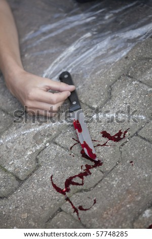 crime scene - female hand with bloody knife on the ground