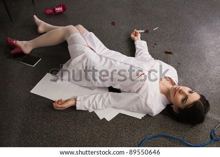 Crime scene imitation. Nurse lying on the floor