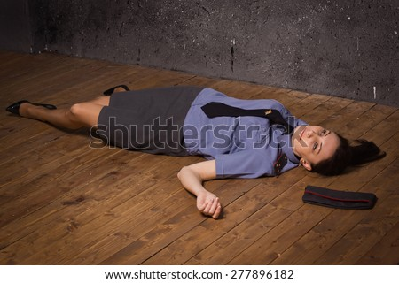 Crime scene imitation  Woman police officer lying on a floor