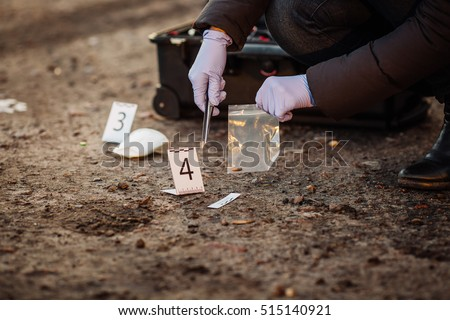 Crime scene investigation - collecting bullet of pistol on the ground - Shutterstock ID 515140921