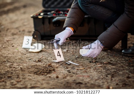 Crime scene investigation - collecting bullet sleeve of pistol on the ground - Shutterstock ID 1021812277