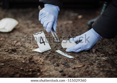 Crime scene investigation - collecting bullet sleeve of pistol on the ground - Shutterstock ID 515029360