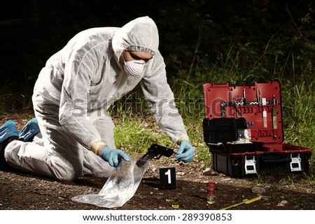 Crime scene investigation - collecting pistol and cartridges by technician